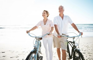senior citizen couple enjoying the beach on bicycles